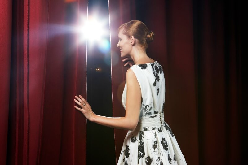IMG: woman standing behind theatre curtain