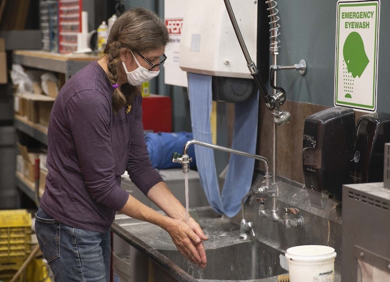a print production specialist washing her hands.