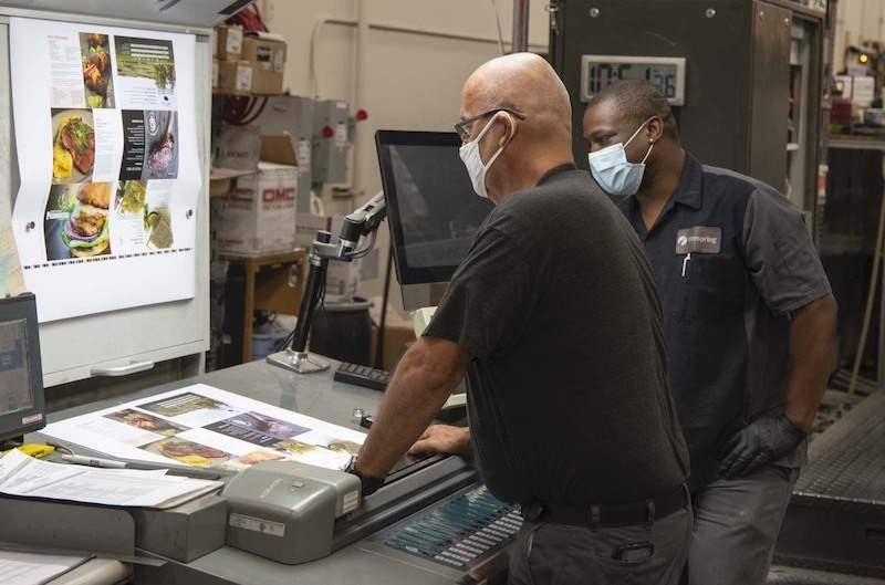 two print production team members discussing a project.